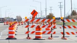 Orange barrels, barricades, and signs blocking a road