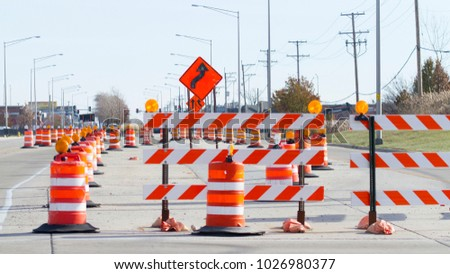Orange barrels, barricades, and signs blocking a road