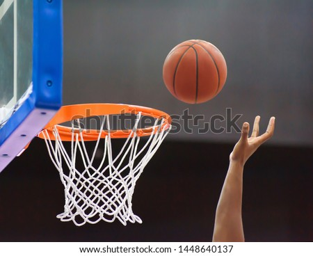 Orange basketball ball flying into the basketball hoop