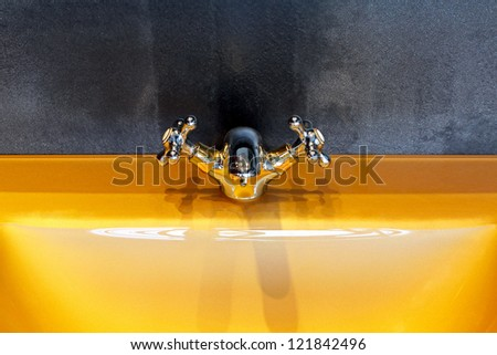 Orange bathroom sink and retro style faucet