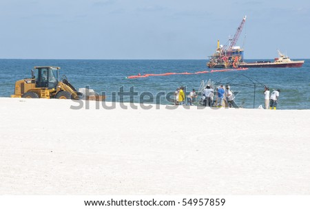 ORANGE BEACH, AL - JUNE 10:  Oil spill workers attempt to clean up oil froma  beach in a tourist resort area on June 10, 2010 in Orange Beach, AL. The beaches are empty except for workers in the height of the tourism season.