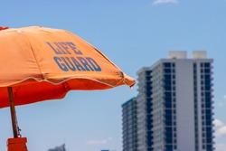 Orange beach life guard umbrella with coastal tourism hotel skyscraper reaching into the blue sky