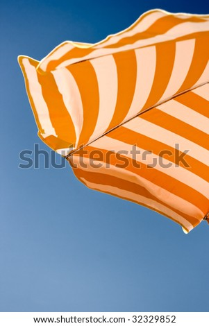 Orange beach umbrella over blue sky background. Space for copy. Jpeg file with clipping path included.