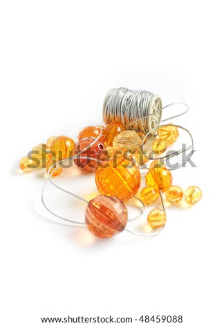orange beads and silver string isolated on white background