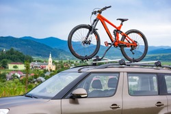 Orange bicycle mounted to the roof of a car on the background of beautiful mountain landscape