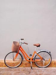 orange bicycle on gray walls