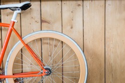 orange bicycle parked with wood wall, close up image part of bicycle