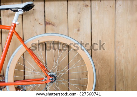orange bicycle parked with wood ...
