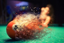 Orange billiard ball splits into particles and debris upon impact