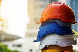 Orange, blue,  white and yellow hard safety helmet hat. Engineer, Construction and Safety Concept. Copy Space.