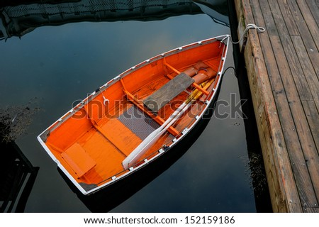 Orange boat in peaceful  water tethered to a dock clear water, row boat, orange