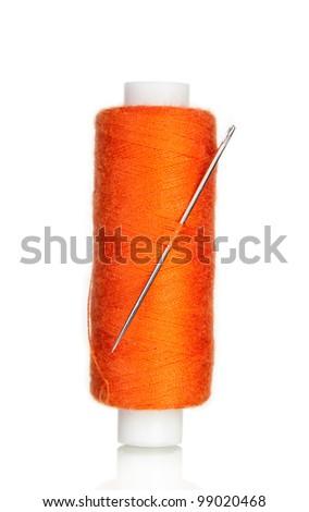 orange bobbin thread with needle isolated on white