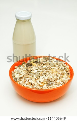 Orange bowl of cereal with a glass bottle of  milk.
