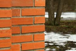 orange brick brick wall with blurred park background