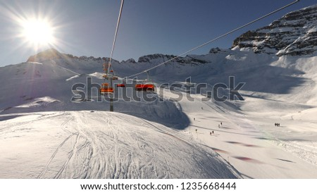 Orange bubble ski chair lift above slopes with pillar and sun reflections on horizon before sunset in Zugspitze ski area in Germany near Garmisch-Partenkirchen #1235668444