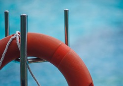orange buoy hanging on stainlesssteel blu and blur background of water