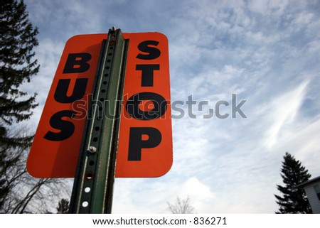 Orange bus stop sign against sky.