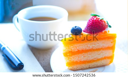 Orange Cake and black coffee  with a brown book and pen set together on the desk. Concept copy space and working with break breaks