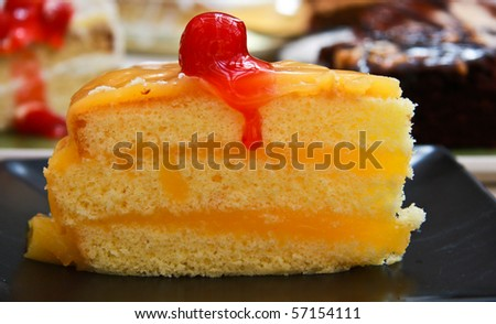 orange cake with cherry on top.