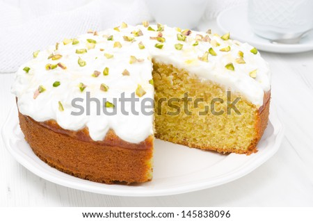 orange cake with Greek yogurt, honey and pistachios in a cut, close-up - stock photo