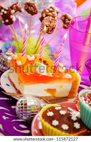 orange cake with three candles on birthday party table for child