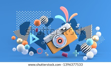 Orange camera surrounded by graphics and colorful balls on a blue background.-3d rendering.