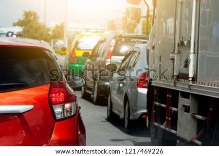 Orange car stop on the road by traffic jam in the city with other cars. #1217469226