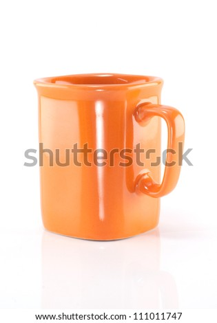 Orange ceramic cup isolated on a white background.