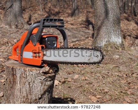 Orange chainsaw and woods