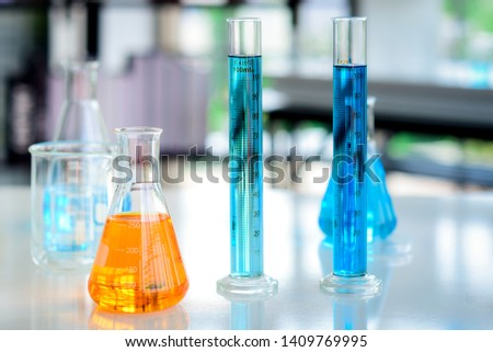 orange Chemicals in flask and blue chemicals in cylinder tubes placed on the table were prepared for chemical experiments in chemical laboratories.