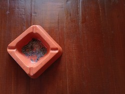 orange cigarette ashtray isolated on wooden background, square or box shape cigarette ash tray