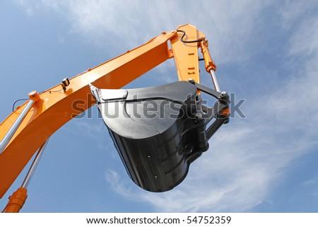 Orange clear excavator bucket against the blue sky