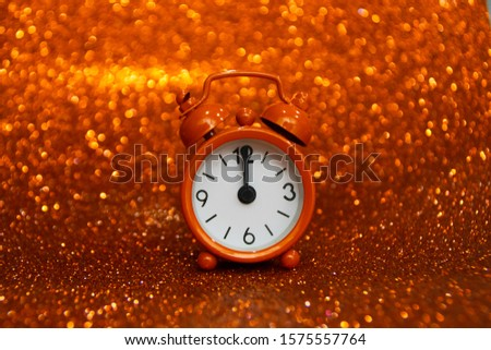 Orange clock showing midnight on a orange background with a glitter. Negative space. Copy space for advertising. Copy space area for text. Happy New Year.