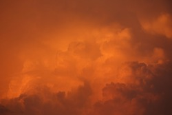 Orange Clouds. Closeup view of a billowing cloud formation illuminated by the setting sun. Shot is graduated diagonally top left to bottom right light orange to darker brown