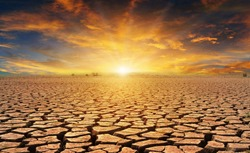 orange cloudy sunset over cracked desert