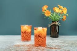 Orange cocktail in vintage crystal glasses with marigold flower bouquet in retro style dark brown glass bottle. Colorful background for celebration decoration design. Vintage wallpaper. Copy space.