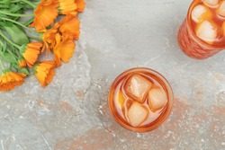 Orange cocktail in vintage crystal glasses with marigold flower bouquet on natural stone background. Colorful backdrop for celebration decoration design. Flat lay style. Copy space.