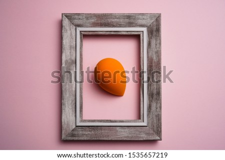 orange color blend beauty sponges on pink background with wooden frame. Makeup tool for applying and blending products such as foundation, concealer. #1535657219