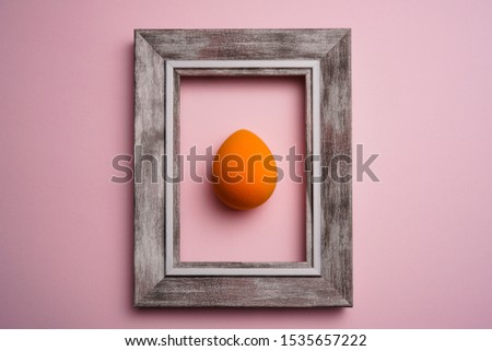 orange color blend beauty sponges on pink background with wooden frame. Makeup tool for applying and blending products such as foundation, concealer. #1535657222