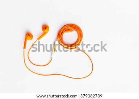 Orange color earphone on background.