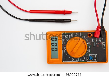 orange color electric Multimeter device on white desk