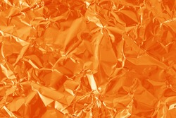 Orange color foil leaf shiny texture, abstract wrapping paper for background and design art work.