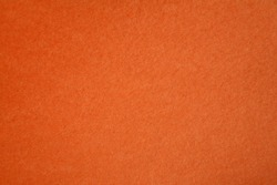 Orange Colored Construction Paper. Close up view of Colored Construction Paper. Backgrounds and Textures. Opacity filter used to lighten and grade the image.