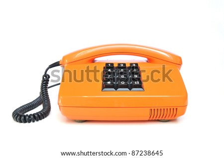Orange colored vintage telephone with phone keypad and receiver on white background