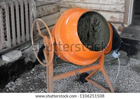 orange concrete mixer prepares cement mortar