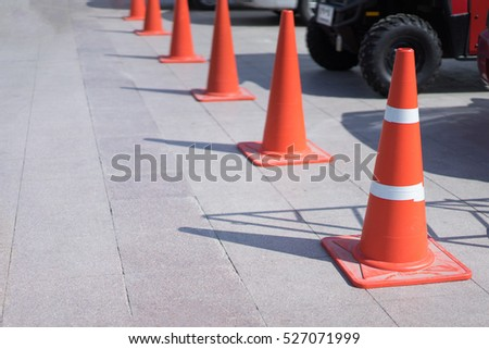 Orange cones in the parking lot with the car in airport. #527071999