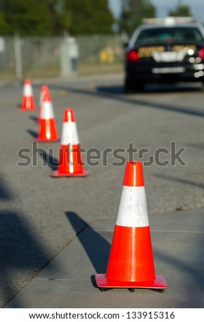 orange cones set up to direct traffic around a police car at a collision scene.