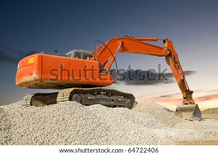 Orange construction digger at work against an evening sky - stock photo
