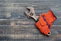 Orange construction gloves in which the monkey wrench is clamped. Tool kit, monkey wrench and work gloves on vintage wooden background, top view, copy space for text
