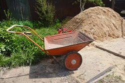 Orange contractor's wheelbarrow or handcart is a helpful tool to carry sand, bricks, wood or other heavy materials in the construction site or household.